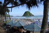 Pengunjung menikmati liburan di Pantai Pulau Merah, Pesanggaran, Banyuwangi, Jawa Timur, Selasa (27/6). Pada H+1 Lebaran kawasan wisata Pulau Merah ramai pengunjung. Antara Jatim/Seno/zk/17.