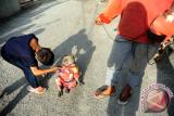 Seekor monyet disalami seorang anak usai melakukan atraksi di Medan, Sumatra Utara, Minggu (2/7). Meski Kementerian Kehutanan telah mengeluarkan larangan eksploitasi hewan untuk komersial, atraksi topeng monyet tersebut masih sering digelar karena dinilai dapat menghasilkan uang sebesar puluhan ribu rupiah per hari. ANTARA FOTO/Jessica Helena Wuysang/17