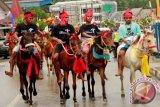 Warga pemilik kuda mengikuti Parade 1.001 Kuda Sandelwood etape ketiga di kota Waikabubak, Sumba Barat NTT, Sabtu (8/7). Parade Kuda tersebut selain untuk meningkatkan kunjungan wisatawan ke tanah Sumba juga bertujuan untuk menjaga nama Sumba yang sudah dikenal lama sebagai pulau penghasil kuda Sandelwood. ANTARA FOTO/Kornelis Kaha/wdy/17.