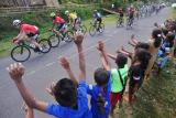 Sejumlah anak menyaksikan para pebalap melintasi Desa Wolowea pada Etape 4 Balap Sepeda Tour de Flores (TDF) 2017 di Borong, NTT, Senin (17/7). Etape 4 balap sepeda TDF 2017 yang berjarak tempuh 170,9 Km rute Mbay-Borong dimenangkan oleh pebalap asal Spanyol Edgar Nohales Nieto dengan catatan waktu 04:47:29. ANTARA FOTO/Nyoman Budhiana/foc/17.