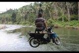 Warga bersama sepeda motornya berada di tali penyeberangan darurat di Sungai Ranteangin antara Desa Maroko dengan Desa Tinokari, Wawo, Kolaka Utara, Sulawesi Tenggara, Jumat (28/7). Warga di Kecamatan Wawo hanya mengandalkan tali penyeberangan darurat untuk ke rumah dan ke kebunnya. ANTARA FOTO/Jojon/pd/17.
