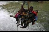 Beberapa pelajar siswa berada di tali penyeberangan darurat di Sungai Ranteangin dibantu personil Kodim 1412 Kolaka saat hendak ke sekolah dari Desa Maroko ke Desa Tinokari, Wawo, Kolaka Utara, Sulawesi Tenggara, Jumat (28/7). Pelajar di Kecamatan Wawo hanya mengandalkan tali penyeberangan darurat untuk pergi ke sekolah mereka. ANTARA FOTO/Jojon/pd/17.