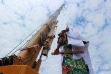 Petugas Badan Penanggulangan Bencana Daerah (BPBD) Pemkab Tuban, Jawa Timur, dengan alat berat 'crane' menutup patung Dewa Perang Kong Co asal Tiongkok dengan kain putih di Kelenteng Kwan Swie Bio, Minggu (6/8). Patung setinggi 30,4 meter itu ditutup dengan kain karena permintaan pengurus kelenteng untuk meredam konflik dengan sejumlah elemen masyarakat yang menolak bangunan patung itu.Antara Jatim/Slamet Agus Sudarmojo/zk/17