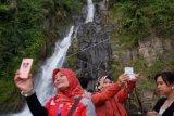 Wisatawan berfoto dengan latar belakang Air Terjun Binangalom, Danau Toba, Toba Samosir, Sumatera Utara, Jumat (27/10). Air terjun yang jatuh langsung ke Danau Toba tersebut merupakan salah satu objek wisata yang banyak dikunjungi wisatawan. ANTARA FOTO/Irsan Mulyadi/ama/17.