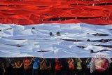 Sejumlah dosen dan mahasiswa membentangkan kain merah putih saat peringatan Hari Sumpah Pemuda di halaman kampus Universitas Surabaya, Surabaya, Jawa Timur, Sabtu (28/10/17). Kegiatan yang melibatkan ribuan mahasiswa dengan menggunakan pakaian adat tersebut sebagai momentum untuk menunjukkan berbeda latar belakang, budaya, agama, etnis, tapi tetap satu kesatuan. (ANTARA FOTO/Umarul Faruq).