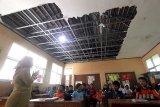 Kegiatan belajar mengajar di kelas yang atapnya rusak di SDN Lebak Pari, Caringin, Bogor, Jawa Barat, Selasa (16/1). Bangunan kelas yang rusak akibat bencana puting beliung menyebabkan atapnya terbawa angin dan sudah satu tahun tidak diperbaiki. Hal tersebut membuat 173 siswa untuk enam kelas, tiga kelas terpaksa harus belajar bergantian, pihak sekolah mengharapkan agar perbaikan segera dilakukan untuk kenyamanan kegiatan belajar mengajar. ANTARA JABAR/Yulius Satria Wijaya
