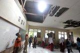 Sejumlah siswa didampingi guru melihat kelas  yang atapnya rusak di SDN Lebak Pari, Caringin, Bogor, Jawa Barat, Selasa (16/1). Bangunan kelas yang rusak akibat bencana puting beliung menyebabkan atapnya terbawa angin dan sudah satu tahun tidak diperbaiki. Hal tersebut membuat 173 siswa untuk enam kelas, tiga kelas terpaksa harus belajar bergantian, pihak sekolah mengharapkan agar perbaikan segera dilakukan untuk kenyamanan kegiatan belajar mengajar. ANTARA JABAR/Yulius Satria Wijaya