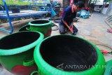 Perajin menyelesaikan proses pembuatan bak sampah berbahan ban bekas di Desa Tambung, Pamekasan, Jawa Timur, Rabu (17/1). Bak sampah yang dikerjakan secara manual itu dihargai Rp75 ribu hingga Rp90 ribu per unit tergantung ukuran. Antara Jatim/Saiful Bahri/zk/18.