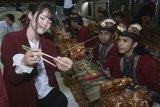Mahasiswa asal Jepang mengajarkan cara menggunakan sumpit kepada mahasiswa Stikom Bali saat melakukan kunjungan di Denpasar, Bali, Kamis (1/2). Kunjungan mahasiswa gabungan tiga universitas asal Kumamoto, Jepang tersebut untuk melakukan pertukaran informasi dan berbagi pengalaman dalam bidang pendidikan dan kebudayaan dengan mahasiswa Indonesia. ANTARA FOTO/Fikri Yusuf/wdy/2018.