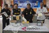 Petugas Bea Cukai dan Badan Narkotika Nasional (BNN) memeriksa barang bukti berupa paket narkotika golongan I yang dikirim lewat Pos dalam konferensi pers di Kantor Bea Cukai Ngurah Rai, Denpasar, Kamis (29/3). Bea Cukai Ngurah Rai menggagalkan pengiriman dua paket narkoba dengan berat total 1,01Kg berisi zat ADB Chminaca dari China dan satu paket seberat 1,01Kg berisi zat AMB Fubinaca dari Belanda yang diduga bahan tembakau gorilla dan berkaitan dengan tersangka yang telah ditangkap beberapa waktu lalu di Denpasar. Antaranews Bali/Nyoman Budhiana/2018.