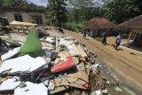 Warga melintas di samping rumah yang rusak akibat pergerakan tanah di desa Randusari, Cibeureum, Kuningan, Jawa Barat, Selasa (27/2). Pergerakan tanah tersebut menyebabkan sedikitnya 40 rumah warga rusak dan warga terpaksa diungsikan ke daerah yang lebih aman. ANTARA JABAR/Dedhez Anggara/agr/18.