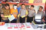 Anggota polisi memeriksa uang palsu saat rilis di Mapolres Jember, Jawa Timur, Selasa (17/4). Polres Jember mengamankan warga Kabupaten Lumajang, Sukamim karena membuat dan mengedarkan uang palsu (upal) antar kabupaten dengan barang bukti mesin cetak/printer, 101 lembar uang pecahan Rp20.000 palsu, 25 lembar kertas fotocopy pecahan Rp20.000 yang belum dipotong, dan pengungkapan ini sekaligus mengantisipasi peredaran upal menjelang Pilkada dan Ramadan. Antara Jatim/Seno/zk/18.