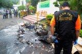 Polisi melakukan olah Tempat Kejadian Perkara (TKP) sesaat terjadi ledakan disela pemusnahan barang bukti hasil kejahatan yang dibakar di kantor Kejaksaan Negeri Makassar, Sulawesi Selatan, Rabu (11/4). Kejadian tersebut melukai dua orang, dan diduga ledakan tersebut dipicu baterei ponsel yang dibakar bersamaan dengan kosmetik yang mengandung bahan kimia. ANTARA FOTO/Darwin Fatir/foc/18.
