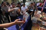 Kapolda Jatim Irjen Pol Machfud Arifin (kedua kiri) menunjukkan barang bukti minuman keras (miras) yang berhasil disita selama Operasi Tumpas Narkoba Semeru 2018 di Polda Jatim, Surabaya, Jawa Timur, Rabu (25/4/2018). Sebanyak 50.070 botol miras berbagai jenis dan merek disita Polda Jatim, Polrestabes Surabaya, Polres Pelabuhan Tanjung Perak Surabaya dan Polresta Sidoarjo dalam operasi yang digelar selama 10 hari tersebut. (ANTARA FOTO/Didik Suhartono)