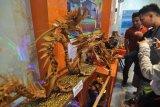 Pengunjung melihat kerajinan tulang ikan yang dibentuk menyerupai seekor naga yang dipamerkan di Palu, Sulawesi Tengah, Senin (16/4). Selain bernilai ekonomis, sampah yang didaur ulang menjadi berbagai benda itu juga dapat mengurangi pencemaran lingkungan.  (ANTARA FOTO/Mohamad Hamzah)