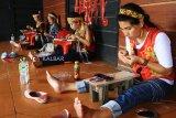 Empat perempuan perajin etnik Dayak merangkai manik-manik kreasi, di arena Pekan Gawai Dayak ke-33 di Rumah Radakng Pontianak, Kalbar, Selasa (22/5). Manik-manik yang dapat dikreasikan menjadi dompet, dasi, gelang, rompi dan baju dengan warna dominan kuning dan merah tersebut, merupakan salah satu kerajinan unggulan suku Dayak Kalbar. ANTARA FOTO/HS Putra/jhw/18