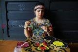 Seorang perempuan perajin etnik Dayak merangkai manik-manik kreasi, di arena Pekan Gawai Dayak ke-33 di Rumah Radakng Pontianak, Kalbar, Selasa (22/5). Manik-manik yang dapat dikreasikan menjadi dompet, dasi, gelang, rompi dan baju dengan warna dominan kuning dan merah tersebut, merupakan salah satu kerajinan unggulan suku Dayak Kalbar. ANTARA FOTO/HS Putra/jhw/18