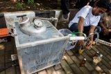 Aktivis Gerakan Tarik Plastik (Get Plastic) menunggu hasil pembakaran plastik dari mesin GP 007 untuk dijadikan bahan bakar minyak jenis premium saat pelatihan dan sosialisasi pengolahan sampah plastik di Bandung, Jawa Barat, Senin (21/5/2018). Gerakan Tarik Plastik (Get Plastic) merupakan kampanye peduli sampah plastik di 15 kota di pulau Jawa dan Bali untuk menggerakan masyarakat agar lebih peduli terhadap lingkungan terutama sampah plastik. (ANTARA FOTO/M Agung Rajasa)