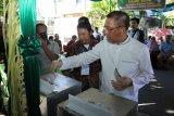 Calon Gubernur Kalbar, Sutarmidji (kanan) memasukkan surat suara ke kotak usai pencoblosan Pilgub Kalbar di TPS 006, Kelurahan Sungai Beliung, Pontianak, Rabu (27/6). Dalam Pilgub Kalbar 2018 yang diikuti tiga pasangan calon dan digelar di 14 kabupaten/kota se-Kalbar tersebut, memperebutkan 3.436.127 suara. ANTARA FOTO/Sheravim/jhw/18