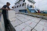 Petugas membongkar muatan truk berisi logistik Pilkada Jatim 2018 untuk dimuat ke kapal KM Sabuk Nusantara 56 di Dermaga Jamrud Utara, Pelabuhan Tanjung Perak, Surabaya, Jawa Timur, Kamis (21/6/2018). Logistik Pilkada Jatim 2018 tersebut dikirim ke Pulau Masalembo yang sebelumnya sempat tertahan sejak Selasa (19/6/2018) akibat cuaca buruk di Laut Jawa bagian timur dan perairan Masalembo. (ANTARA FOTO/Didik Suhartono)