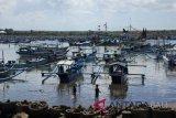 Anak nelayan berjalan di dekat perahu yang ditambatkan di Pantai Grajagan, Purwoharjo, Banyuwangi, Jawa Timur, Kamis (14/6). Ratusan perahu nelayan ditambatkan atau tidak melaut menjelang Hari Raya Idul Fitri 1439 H dan akan kembali melaut pada H+7 Lebaran. ANTARA FOTO/Seno/wdy/2018