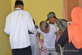 Petugas KPPS di TPS 3 Desa Molantadu Kecamatan Tomilito Kabupaten Gorontalo Utara memindahkan kotak suara untuk melayani pasien sakit sebanyak 4 orang di TPS itu. (Foto ; Shanty)