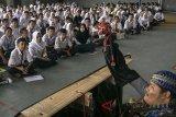 Sejumlah siswa menyaksikan aksi wayang motekar tentang bahaya narkoba saat Deklarasi Pelajar Anti Narkoba di SMAN 9 Bandung, Jawa Barat, Rabu (18/7). Kegiatan yang bekerjasama dengan BNN kota Bandung dan Sehati tersebut bertujuan memberikan penyuluhan dan edukasi kepada pelajar tentang bahaya penyalahgunaan narkoba dan pencegahan peredaran narkoba di lingkungan sekitar. ANTARA JABAR/Novrian Arbi/agr/18