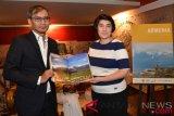 Dirut Perum LKBN Antara Meidyatama Suryodiningrat (kiri) menyerahkan buku fotografi