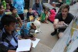 Relawan dari Gereja Yesus Kristus dari Orang-orang Suci Zaman Akhir, Elder Fradella (kanan) mengajar bahasa Inggris kepada anak-anak di sela-sela acara Festival Bule Ngecat di Kampung Inggris Dolly, Putat Jaya, Surabaya, Jawa Timur, Jumat (3/8). Kegiatan yang diisi dengan belajar bersama bahasa Inggris dan pengecatan rumah warga tersebut bertujuan untuk mengembangkan kawasan eks lokalisasi Dolly menjadi kawasan melek bahasa Inggris dan wisata edukasi. Antara Jatim/Moch Asim/18.