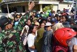 Petugas mengatur pangantre daging kurban di Masjid At-Taqwa Kota Madiun, Jawa Timur, Rabu (22/8). Panitia penyembelihan hewan kurban di masjid tersebut menyembelih 10 ekor lembu dan 12 ekor kambing yang dagingnya dibagikan kepada warga sekitar. Antara Jatim/Siswowidodo/mas/18.
