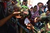 Warga mengantre daging kurban di Masjid At-Taqwa Kota Madiun, Jawa Timur, Rabu (22/8). Panitia penyembelihan hewan kurban di masjid tersebut menyembelih 10 ekor lembu dan 12 ekor kambing yang dagingnya dibagikan kepada warga sekitar. Antara Jatim/Siswowidodo/mas/18.
