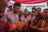 Menteri Riset Teknologi dan Pendidikan Tinggi Mohamad Nasir (kedua kiri), mantan Presiden B.J. Habibie (tengah) dan Gubernur Riau Arsyadjuliandi Rachman (ketiga kanan) melihat seorang peserta yang mengoperasikan tangan palsu pada acara puncak peringatan Hari Kebangkitan Teknologi Nasional (Hakteknas) ke-23 di Pekanbaru, Riau, Jumat (10/8/2018). Pameran hasil inovasi dan penemuan teknologi dari semua bidang itu berlangsung di Kota Pekanbaru hingga Minggu (12/8/2018) mendatang. ANTARA FOTO/Rony Muharrman/foc/18.
