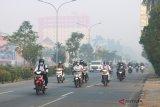 Sejumlah pengendara melintasi jalan yang diselimuti kabut asap di Pontianak, Kalbar, Senin (20/8). BNPB menyatakan bahwa hingga kini masih terpantau 526 titik api di Kalbar yang berasal dari karhutla di sejumlah kabupaten di Kalbar, yang mengakibatkan kabut asap tebal menyelimuti Kota Pontianak. ANTARA FOTO/Jessica Helena Wuysang/18
