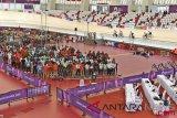 Sejumlah atlet balap sepeda berlatih saat berlangsungnya salat Jumat di dalam track di Velodrome Rawamangun, Jakarta, Jumat (31/8/2018). (ANTARA FOTO/INASGOC/Jefri Tarigan)