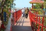 Pengunjung menikmati panorama pantai dan hutan mangrove di Pantai Talang Siring, Pamekasan, Jawa Timur, Minggu (19/8). Pemerintah mengembangkan hutan mangrove guna meningkatkan kunjungan di kawasan wisata pantai tersebut. Antara Jatim/Saiful Bahri/mas/18.