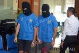Petugas polisi menggiring tersangka warga negara Inggris berinisial ZBT (kiri) dan warga negara Chile berinisial VMOR (kedua kanan) saat gelar perkara di Bea Cukai Ngurah Rai, Bali, Rabu (1/8). Petugas Bea Cukai berhasil menggagalkan penyelundupan narkoba dengan barang bukti milik VMOR sebanyak 3 gram biji ganja dan milik ZBT 3,55 gram tembakau iris yang disembunyikan di dalam kemasan rokok untuk berusaha mengelabui petugas. ANTARA FOTO/Wira Suryantala/wdy/2018.