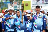 Direktur Wahid Institute, Yenny Wahid (tengah) didampingi Ketua Panitia Pelaksana Asian Para Games (Inapgoc), Raja Sapta Oktohari (kanan) dan Kapolda Kalbar, Irjen Pol Didi Haryono (kiri), mengangkat api obor Asian Para Games 2018 di Alun-Alun Sungai Kapuas, Pontianak, Kalbar, Rabu (19/9). Pawai Obor Asian Para Games 2018 melintasi garis khatulistiwa di Pontianak, sebelum nantinya berlanjut ke Medan pada 23 September. ANTARA FOTO/Jessica Helena Wuysang/18