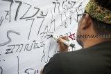Warga menulis aksara sunda di kain saat pemecahan Original Rekor Indonesia (ORI) di Batujaya, Karawang, Jawa Barat, Jumat (21/9). Penulisan aksara sunda sepanjang 385 meter berhasil memecahkan rekor ORI yang bertujuan untuk melestarikan aksara sunda di Indonesia. ANTARA JABAR/M Ibnu Chazar/agr/18.