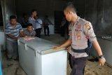 Sejumlah anggota kepolisian dari Polres Sanggau membawa lemari pendingin berisi daging beku ilegal dari gudang penampungan di Dusun Kuya, Desa Lubuk Sabuk, Kecamatan Sekayam, Kabupaten Sanggau, Kalbar, Sabtu (20/10/2018). Jajaran Polres Sanggau menyita 0,5 ton daging sapi, ayam dan ikan ilegal asal Malaysia yang sudah dibekukan dalam lemari pendingin karena tidak dilengkapi dengan dokumen resmi. ANTARA FOTO/Agus Alfian/jhw