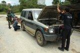 Seorang petugas Unit K9 Bea Cukai Kantor Wilayah Kalimantan Bagian Barat (Kanwil) Kalbagbar memeriksa kendaraan dari Malaysia yang hendak masuk ke Indonesia melalui Perbatasan Jagoi Babang di Kabupaten Bengkayang, Kalbar, Rabu (17/10/2018). Pemeriksaan terhadap kendaraan pelintas batas negara yang dilakukan secara manual oleh Tim Bea Cukai Kanwil Kalbagbar bersama TNI AD itu karena perbatasan Jagoi Babang belum dilengkapi alat X-Ray. ANTARA FOTO/HS Putra/jhw
