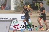 Atlet Triathlon Eva Desiana (kiri) dan pembalap Rio Haryanto (kanan) mengikuti Herbalife Bali International Triathlon 2018 di Sanur, Denpasar, Bali, Minggu (21/10/2018). Herbalife Bali International Triathlon 2018 diikuti 2.250 orang peserta dari berbagai negara, terbagi dalam tiga kategori utama yaitu, Olympic Distance Course (renang 1,5 km, sepeda 40 km, lari 10 km), Sprint Distance Course (renang 500m, sepeda 20 km, lari 5 km) dan 5 km Fun Run. ANTARA FOTO/Fikri Yusuf/wdy/2018