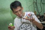 Perajin menunjukkan rakitan robot mainan di Kecamatan Jatiluhur, Purwakarta, Jawa Barat, Sabtu (24/11/2018). Pembuatan robot mainan tersebut menggunakan limbah elektronik. ANTARA JABAR/M Ibnu Chazar/agr.