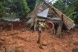 Warga membawa sepeda yang masih bisa diselamatkan di rumahnya yang tertimbun material tanah longsor di Desa Bojongsari, Kabupaten Tasikmalaya, Jawa Barat, Kamis (8/11/2018). Curah hujan yang tinggi di daerah Tasikmalaya Selatan mengakibatkan sembilan rumah tertimbun tanah longsor dan sebanyak 2.045 jiwa terdampak bencana longsor serta banjir dari 10 Desa yang ada di Kabupaten Tasikmalaya. ANTARA JABAR/Adeng Bustomi/agr.