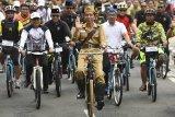 Presiden Joko Widodo mengenakan baju pejuang Bung Tomo (tengah) didampingi Kepala Staf Presiden Moeldoko (kiri) dan Gubernur Jawa Barat Ridwan Kamil (kedua kanan) menyapa warga ketika mengikuti kegiatan sepeda bersama dengan tema Bandung Lautan Sepeda di Bandung, Jawa Barat, Sabtu (10/11/2018). Kegiatan yang diikuti ribuan peserta tersebut dalam rangka memperingati Hari Pahlawan. ANTARA JABAR/Wahyu Putro A/agr.