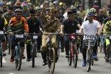 Presiden Joko Widodo (tengah) didampingi Gubernur Jawa Barat Ridwan Kamil (kanan) menyapa warga ketika mengikuti kegiatan sepeda bersama dengan tema Bandung Lautan Sepeda di Bandung, Jawa Barat, Sabtu (10/11/2018). Kegiatan yang diikuti ribuan peserta tersebut dalam rangka memperingati Hari Pahlawan. ANTARA JABAR/Wahyu Putro A/agr.