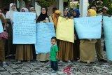 Sejumlah guru honor Kategori 2 (K2) yang tergabung dalam Asosiasi Gurun Aceh membubuhkan tandatangan pada spanduk saat menggelar aksi damai di gedung DPRA, Banda Aceh, Rabu (12/12/2018). Guru honor K2 yang sudah lulus tes CPNS Panitia Seleksi Nasional mendesak DPRA memperjuangkan nasibnya agar pemerintah pusat dan pemerintah Aceh menerbitkan SK pengangkatan sebagai PNS dan menolak rencana penetapan Pegawai Pemerintah dengan Perjanjian Kerja (P3K) oleh pemerintah pusat. (Antara Aceh/Ampelsa)