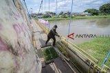 Warga menyeberangi Sungai Citarum menggunakan jembatan gantung yang rusak di Rancamanyar, Kabupaten Bandung, Jawa Barat, Minggu (30/12/2018). Jembatan penghubung antar kecamatan tersebut rusak setelah jadi akses utama sepeda motor saat banjir merendam jalan raya beberapa hari lalu. ANTARA JABAR/Raisan Al Farisi/agr.