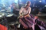 Perajin menyelesaikan proses pembuatan batik di Desa Klampar, Pamekasan, Jawa Timur, Rabu (30/01/2019). Pada tahun ini, Pemprov Jatim menargetkan 27.000 UMKM di Jawa Timur Masuk pasar daring.  Antara Jatim/Saiful Bahri/ZK