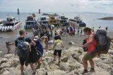 Sejumlah wisatawan antre naik ke kapal cepat untuk menyeberang ke Pulau Nusa Penida dan Nusa Lembongan di Pantai Sanur, Denpasar, Bali, Jumat (25/1/2019). Meskipun telah dikeluarkan peringatan dini terhadap angin kencang dan gelombang tinggi di perairan selatan Bali hingga beberapa hari ke depan, tidak menurunkan aktivitas penyeberangan dan wisata ke pulau tersebut dan masih berjalan normal. ANTARA FOTO/Nyoman Hendra Wibowo/nym