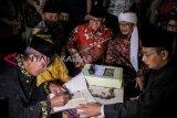 Gubernur DKI Jakarta Anies Baswedan (kedua kiri) dan tokoh agama Aa Gym (kedua kanan) memberikan buku nikah seusai menjadi saksi di acara nikah massal di Jakarta, Senin (31/12/2018). Sebanyak 557 peserta mengikuti nikah massal yang digelar Pemprov DKI Jakarta dalam rangka menyambut malam pergantian tahun 2019. ANTARA FOTO/Putra Haryo Kurniawan/pras.